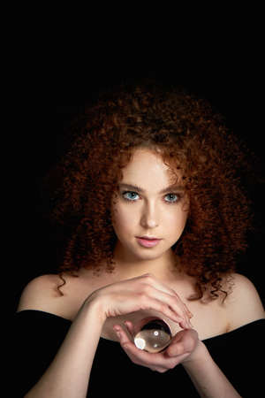 A girl with lush curly red hair. Holds in his hands a glass globe. Mystery,a premonition of the future.