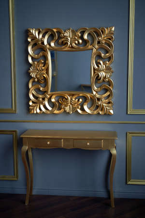 A mirror and a table gold color of. On the background of the classic gray walls. Palace interior