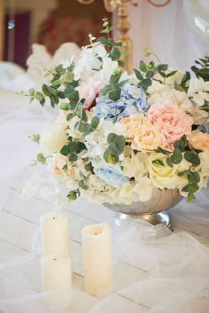 Floor metal vase with flowers and white candles. Romantic atmosphere