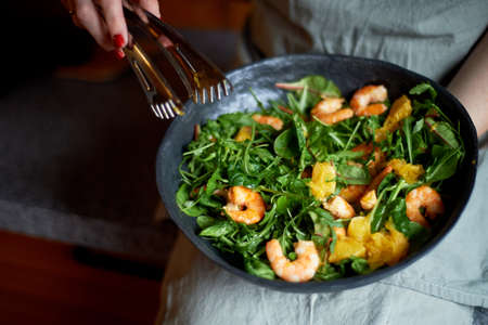 Healthy diet. Salad of arugula, tiger prawns and oranges. Light dish with seafood. Diet menu. Hands interfere salad Stock Photo
