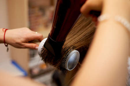 Hair styling a round brush. Drying and laying on a round comb. 版權商用圖片