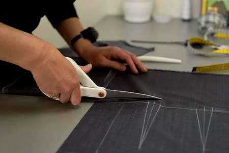 Master cuts fabric. Nesting. Suiting fabric marked with white chalk. Cutting and sewing