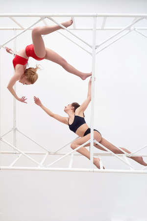 Gymnasts , pairs of poses. In red and black swimsuit on white background. Metal high construction. Plastic body.