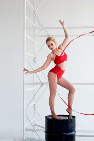 Gymnast in a red swimsuit is on a black barrel. On light background. Red ribbon. Banco de Imagens