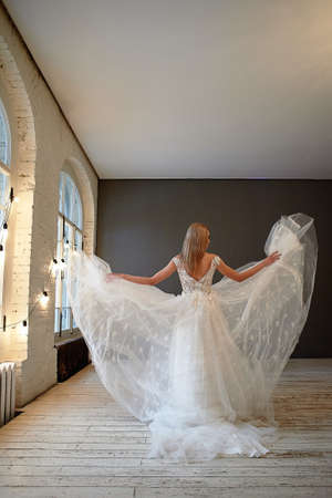 Beautiful lace dress, perfectly sitting on the figure. A beautiful bride stands in a loft-style room, throws up a skirt of a lush wedding dress. Stock Photo