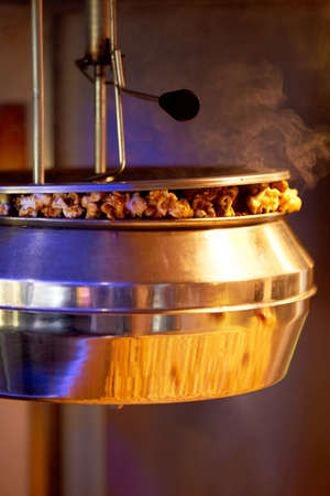 Cooking steaming popcorn in the cinema machine. Metal bowl and steam.