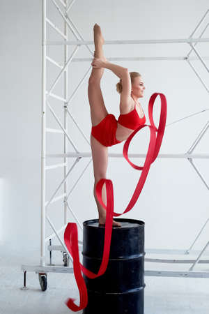 Gymnast in a red swimsuit is on a black barrel. On light background.Red ribbon.