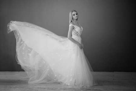 Beautiful lace dress, perfectly sitting on the figure. A beautiful bride stands in a loft-style room, throws up a skirt of a lush wedding dress. Zdjęcie Seryjne
