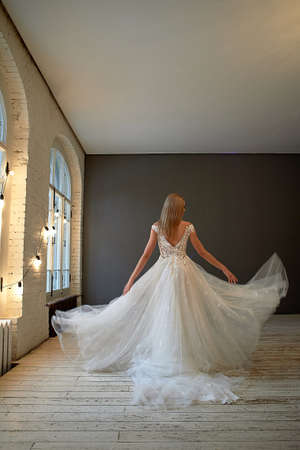 Beautiful lace dress, perfectly sitting on the figure. A beautiful bride stands in a loft-style room, throws up a skirt of a lush wedding dress. 版權商用圖片