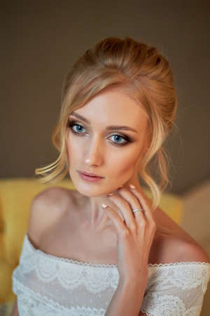 Portrait of a beautiful miniature bride in a lace dress. Hair with curls. Emphasis in make-up on the eyes.Blonde Stock Photo