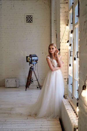 The bride in a white lace dress with embroidered bodice, indoors in loft style. Long, flowing, ash-colored hair. Stock Photo
