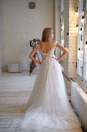 Graceful back of the bride. Looking out the window. Hairstyle - elegant bunch in the French style.