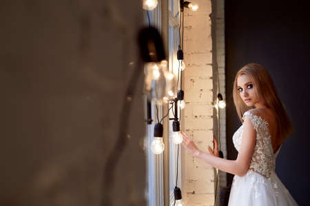The bride in a white lace dress with embroidered bodice, indoors in loft style. Warm next to burning light bulbs.