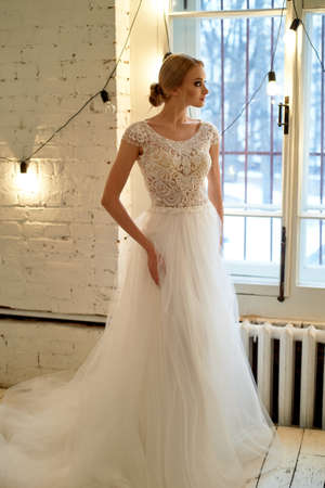 The bride in a white lace dress with embroidered bodice, indoors in loft style. High key.