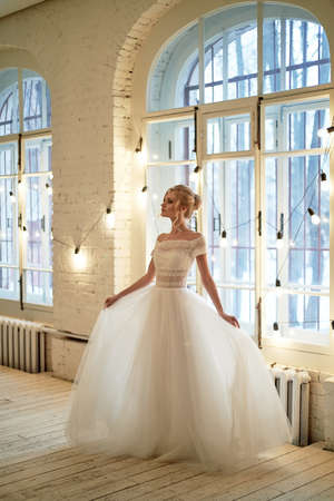 Bride with white dress, with lace top. Hairstyle elegant up-do hair, blonde hair. In a white brick loft-style room.