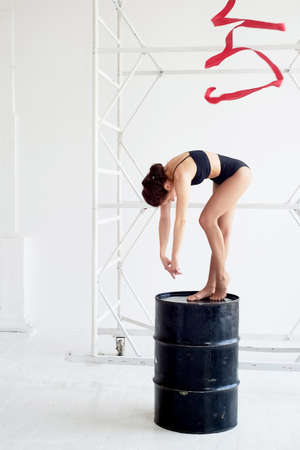 Gymnast in a black swimsuit is on a black barrel. On light background.Red ribbon. 版權商用圖片