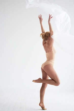 Gymnaste dansant avec un film transparent sur un mur et un sol blancs. Grâce et mode de vie sain.