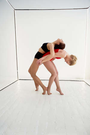 Gymnasts , pairs of poses. In red and black swimsuit on white background. Plastic body, support.