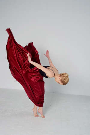A gymnast in a dark top and a red silk skirt. The color of passion, of aggression. Tango. Plastic body, airiness , weightlessness and lightness.