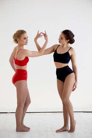 Turner, Posenpaare. Im roten und schwarzen Badeanzug auf weißem Hintergrund. Kunststoffkörper, Stütze.