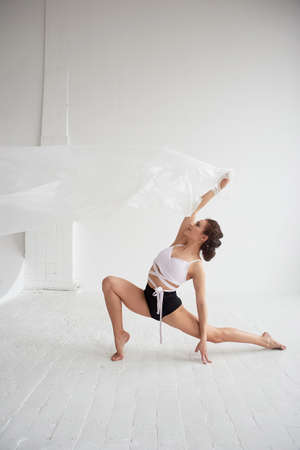 Gymnast dancing with a transparent film on a white wall and floor. Grace and healthy lifestyle.