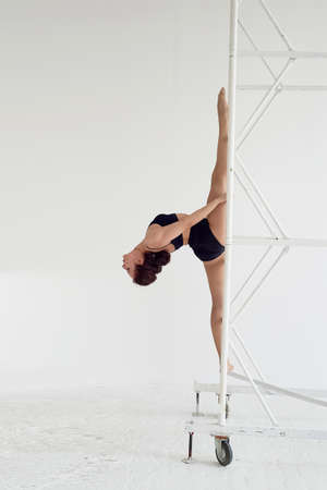 The splits in the air on metal poles. Gymnast in black tights. Flexibility