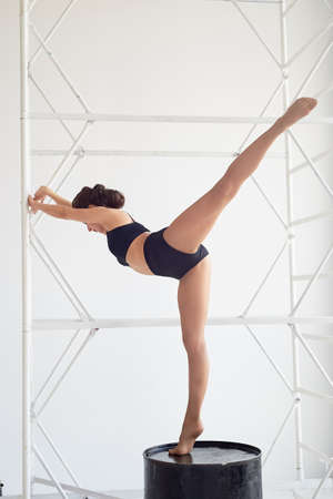 Graceful gymnast stands on a high black barrel , makes complex shapes. Sports, fitness, stretching.