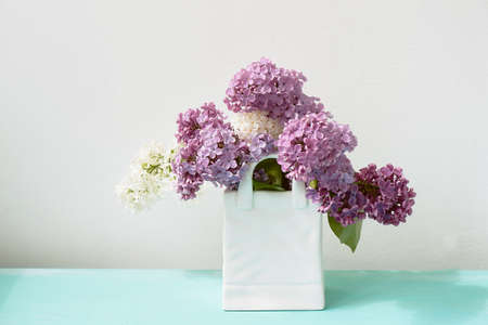 Branches of white and purple lilac. Natural wealth. In a white vase package. Foto de archivo - 123523131