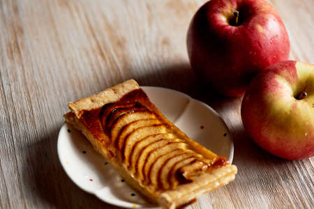 A delicious piece of Apple pie, red apples. Tea party.