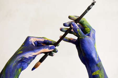 Graceful hands of the artist with a brush. Hands in blue and yellow paint. Creator, creativity. Foto de archivo - 123523168