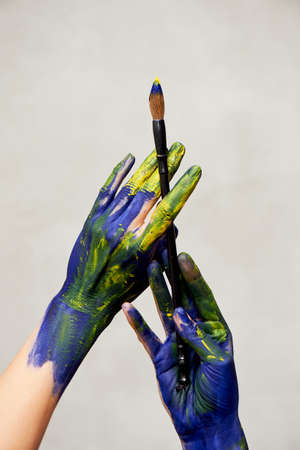 Graceful hands of the artist with a brush. Hands in blue and yellow paint. Creator, creativity. Foto de archivo - 123523169