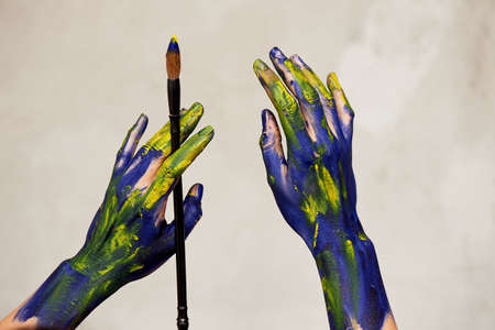 Graceful hands of the artist with a brush. Hands in blue and yellow paint. Creator, creativity. Foto de archivo - 123523171