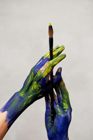 Graceful hands of the artist with a brush. Hands in blue and yellow paint. Creator, creativity. Foto de archivo - 123523170