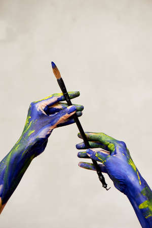Graceful hands of the artist with a brush. Hands in blue and yellow paint. Creator, creativity.