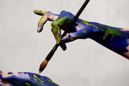 Graceful hands of the artist with a brush. Hands in blue and yellow paint. Creator, creativity. Foto de archivo - 123523174