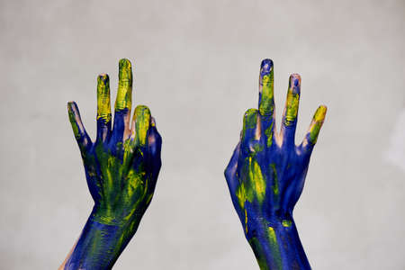 Graceful hands of the artist . Hands in blue and yellow paint. Creator, creativity. Yoga for hands Foto de archivo - 123523176