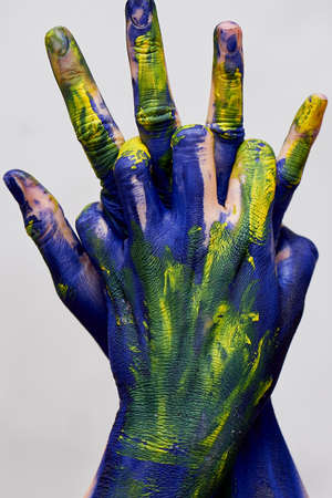 Graceful hands of the artist . Hands in blue and yellow paint. Creator, creativity.Yoga for hands. Fingers locked. Sign of protection and closure. Stock Photo