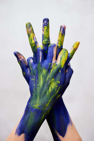 Graceful hands of the artist . Hands in blue and yellow paint. Creator, creativity.Yoga for hands. Fingers locked. Sign of protection and closure. Foto de archivo - 123523177