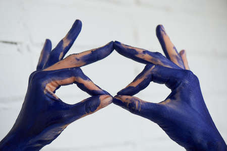 Hands in blue paint, the hands of the artist and creative person. Yoga for the hands.