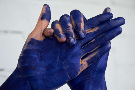 Hands in blue paint, the hands of the artist and creative person. Yoga for the hands. Foto de archivo - 123525217