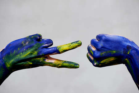 Graceful hands of the artist . Hands in blue and yellow paint. Creator, creativity.Yoga for hands.A game of Rock paper scissors. Rock scissors, hand in paint. Play and win Stock Photo