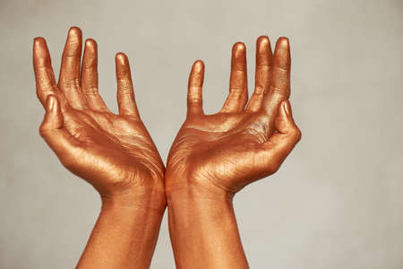 Hands in gold paint, the hands of the artist and creative person. Yoga for hands Foto de archivo - 123525252