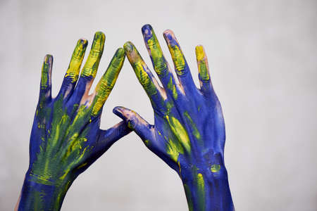 Hands in blue paint with yellow accents, hands of the artist and creative person. Yoga for hands Foto de archivo - 123525268
