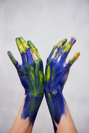 Hands in blue paint with yellow accents, hands of the artist and creative person. Yoga for hands Foto de archivo - 123525270