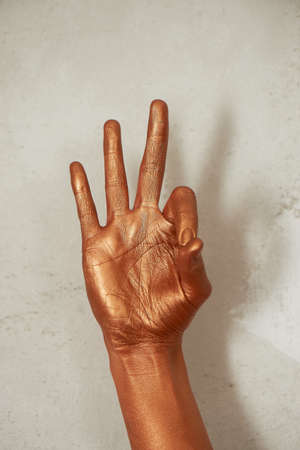 Hands in gold paint, the hands of the artist and creative person. Yoga for hands Banco de Imagens