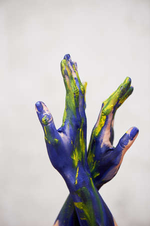 Hands in blue paint with yellow accents, hands of the artist and creative person. Yoga for hands Foto de archivo - 123525283