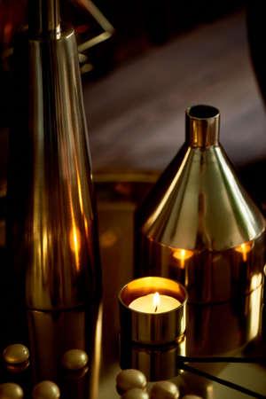 Cozy decor. Gold , burning candles Golden vessels Foto de archivo - 123525303