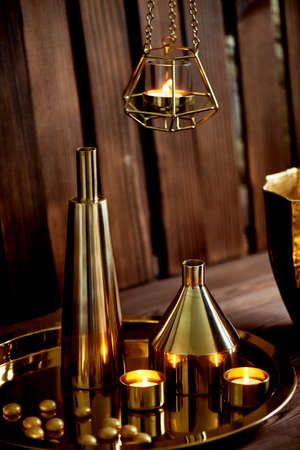 Cozy decor. Gold , burning candles Golden vessels Foto de archivo - 123525307
