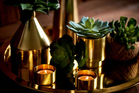 Cozy decor. Gold , burning candles Golden vessels succulents