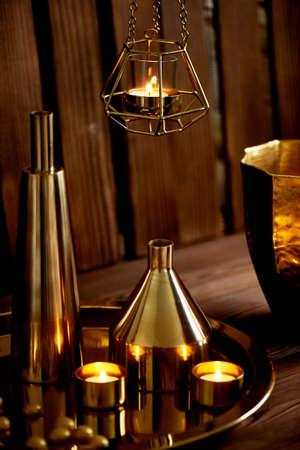 Cozy decor. Gold , burning candles Golden vessels Foto de archivo - 123525316